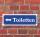 """Schild im Straßenschild-Design """"Toiletten links"""" 30 x10 cm Alu-Verbund"""